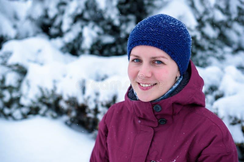 Piękny kobiety dmuchanie w śniegu w sosnowym lesie obraz royalty free