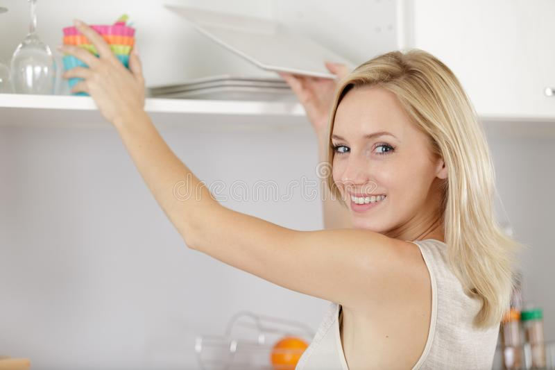 Piękny kobiety dojechanie dla crockery od kuchennej spiżarni fotografia royalty free