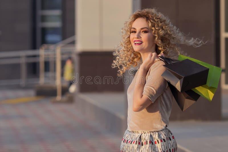Piękny kobiety kręcenie wokoło i ono uśmiecha się z torba na zakupy szczęśliwa dziewczyna z ich zakupami zdjęcia royalty free