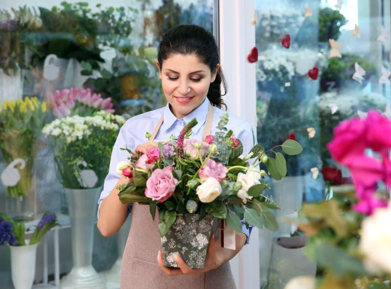 Piękny kobiety kwiaciarni mienia garnek z kwiatami zdjęcie stock