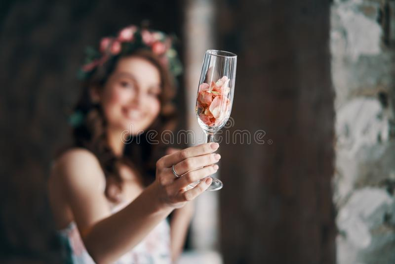 Piękny kobiety mienia wineglass z różanymi płatek otuchami kamera obrazy royalty free