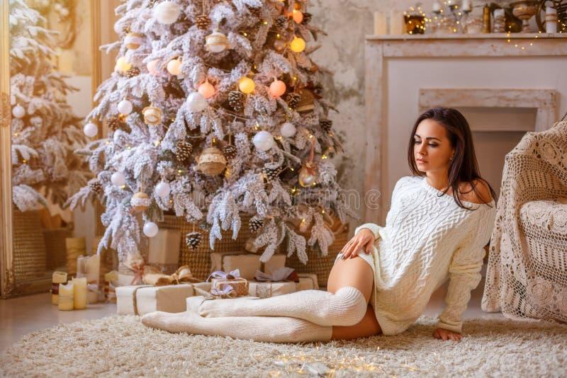 Piękny kobiety obsiadanie blisko choinki na podłoga w białym pulowerze białych leggings i zdjęcia royalty free
