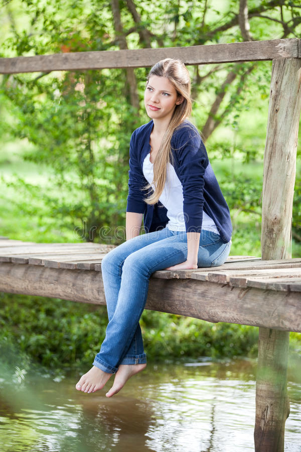 Piękny kobiety obsiadanie Na Drewnianym moscie zdjęcie stock
