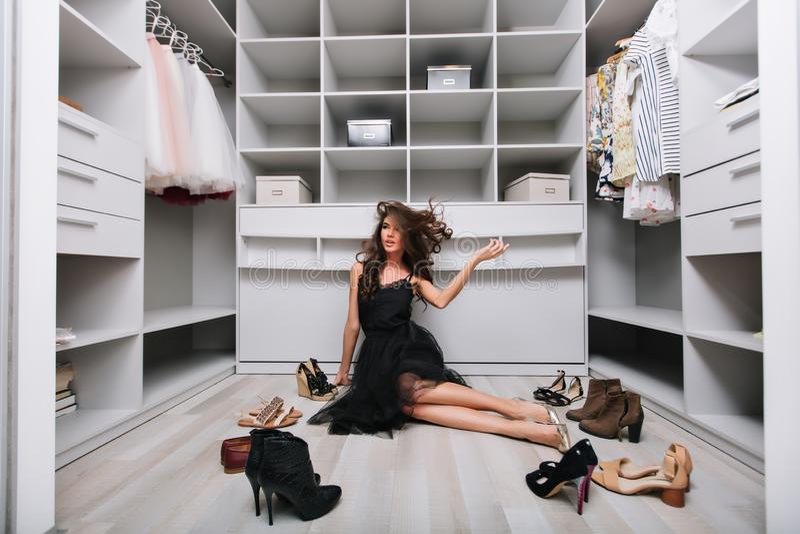 Piękny kobiety obsiadanie na podłodze w eleganckiej garderobie obraz royalty free