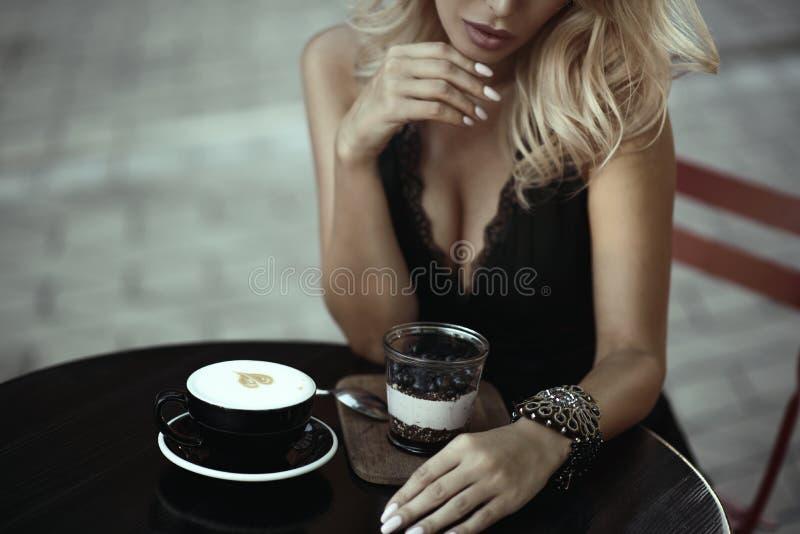 Piękny kobiety obsiadanie w lata cukiernianym mieniu jej ręka pod podbródkiem Filiżanka smakowity piankowaty latte i jagody deser fotografia royalty free