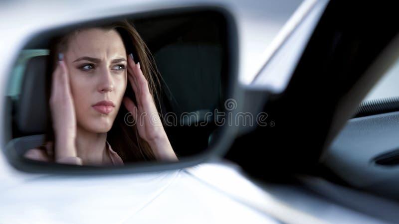 Piękny kobiety obsiadanie w samochodzie, cierpienie od okropnej migreny, nieszczęśliwej zdjęcie royalty free