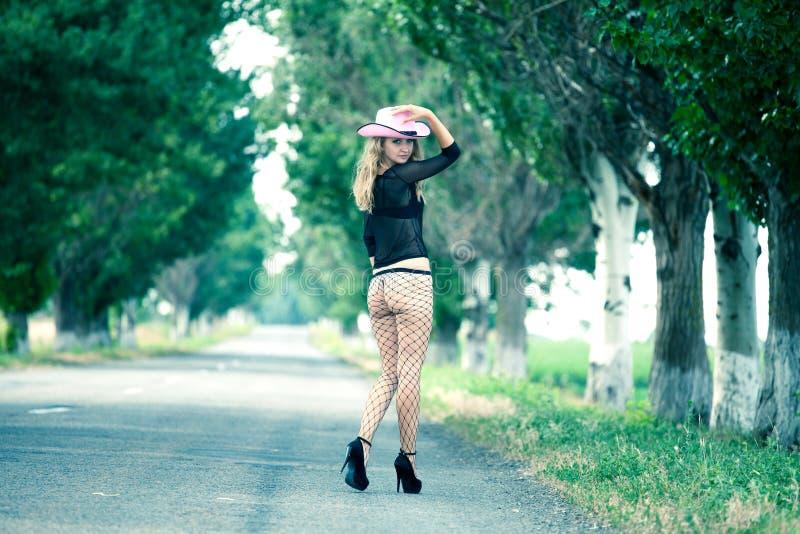 Piękny kobiety odprowadzenie na wiejskiej drodze zdjęcia stock
