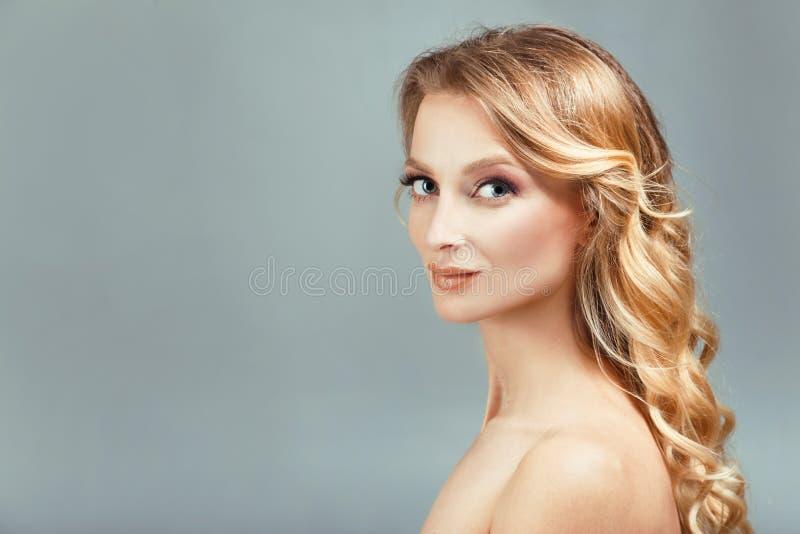Piękny kobiety twarzy zakończenie up tęsk kędzierzawy blondynka włosy studio na beżu fotografia royalty free
