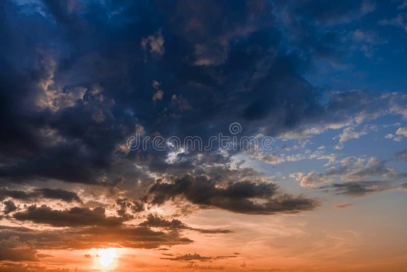 Piękny kolorowy zmierzch z cumulus chmurami z ptakiem zdjęcie stock