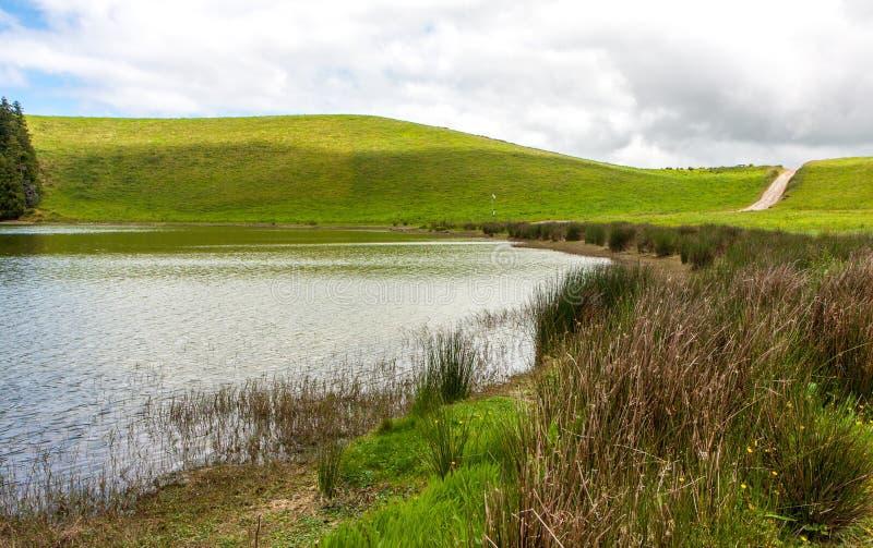 Piękny krajobraz na pogodnym chmurnym dniu z jeziorem, drogą, wzgórzami i roślinami, zdjęcia royalty free