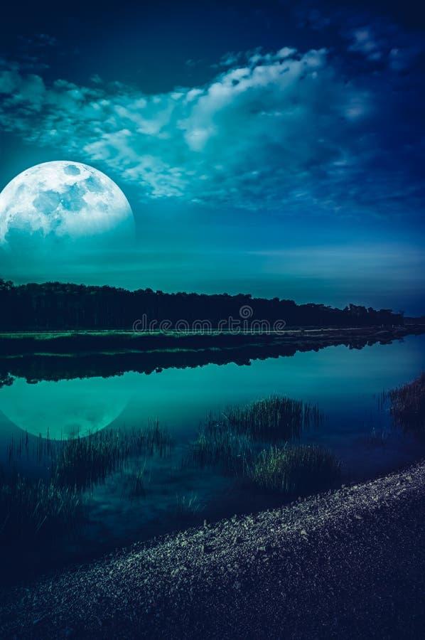Piękny krajobraz niebieskie niebo z obłoczną i super księżyc nad sylwetki drzewa przy brzeg rzekim Spokój natury tło, zdjęcie stock