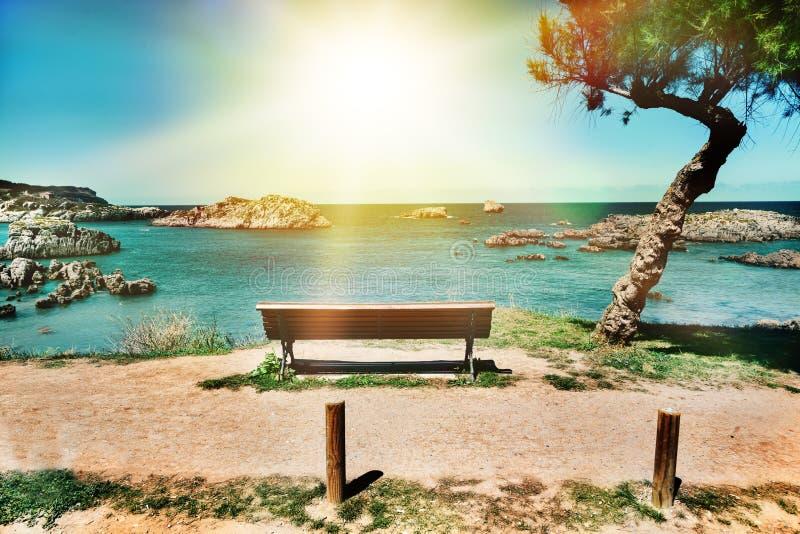 Piękny krajobraz plaża i wybrzeże z górami i roślinnością Osamotniona ławka na falezie stawia czoło dennego Cantabria, Hiszpania zdjęcie royalty free