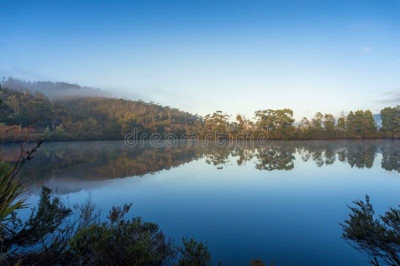 Piękny krajobraz z lustrem jak wod nawierzchniowi odbija drzewa niebo i obrazy stock