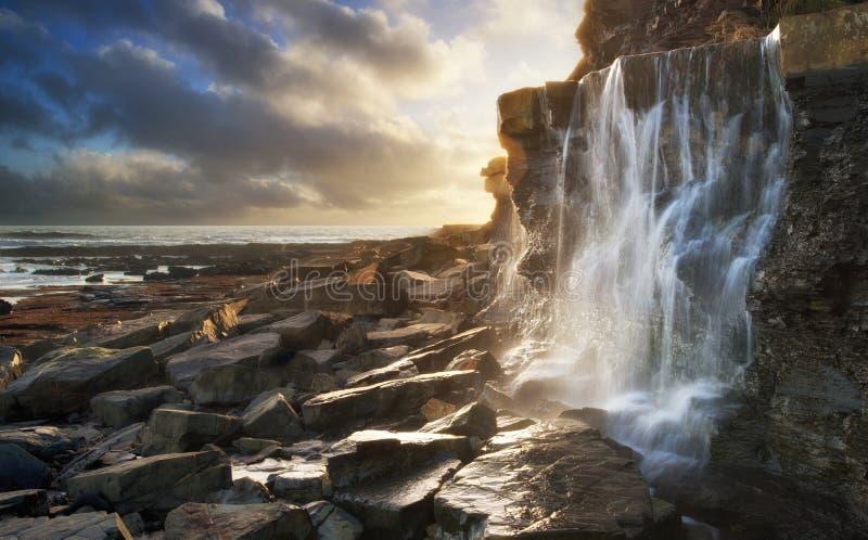 Piękny krajobrazowy wizerunek siklawy spływanie w skały na plaży obraz royalty free