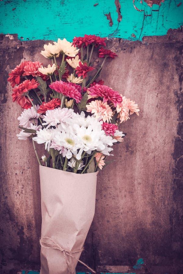 Piękny kwiatu bukiet zawijający w rzemiosło papierze na drewnianym stołowym tle obraz stock
