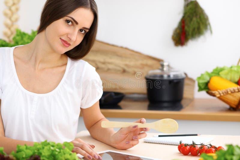 Piękny Latynoski kobiety kucharstwo w kuchni podczas gdy używać pastylka komputer i drewnianą łyżkę Gospodyni domowa znajdujący n fotografia royalty free
