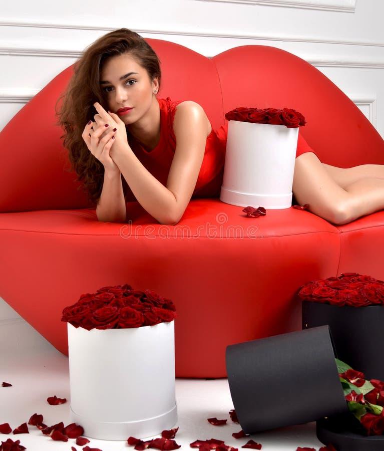 Piękny luksusowy modnej kobiety lying on the beach na czerwonej wargi kanapy leżance zdjęcia stock