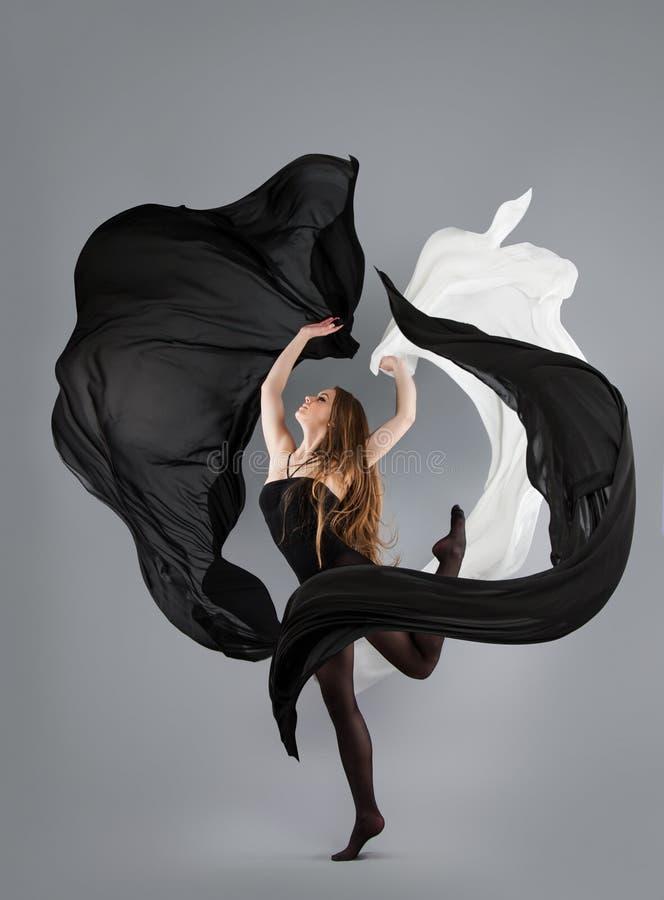 Piękny młoda dziewczyna taniec czarny i biały tkanina w ruchu zdjęcia royalty free