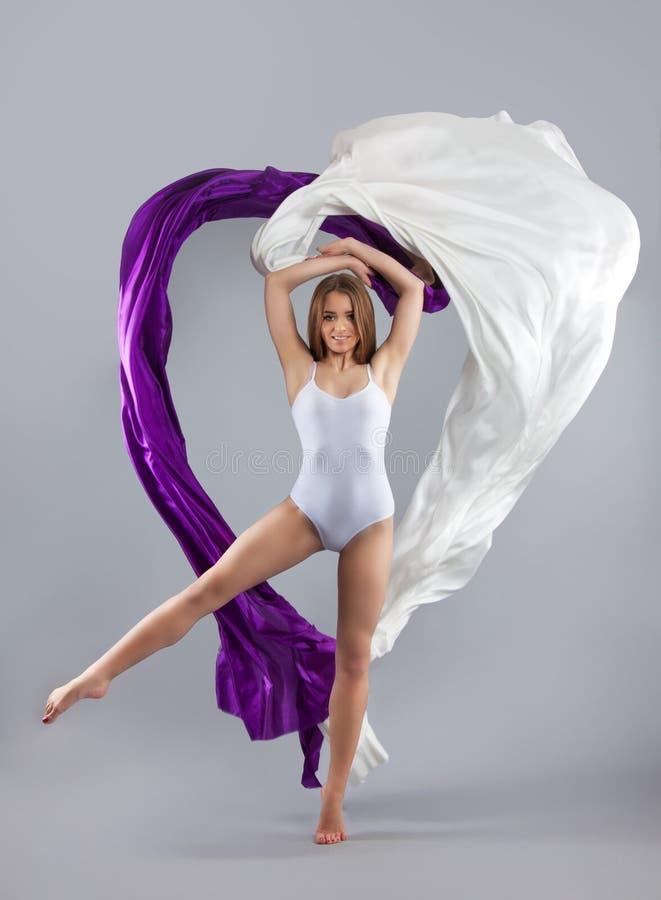 Piękny młoda dziewczyna taniec tkaniny spływanie Dziewczyna rzuca białego i purpurowego płótno Tkanina lata obraz royalty free