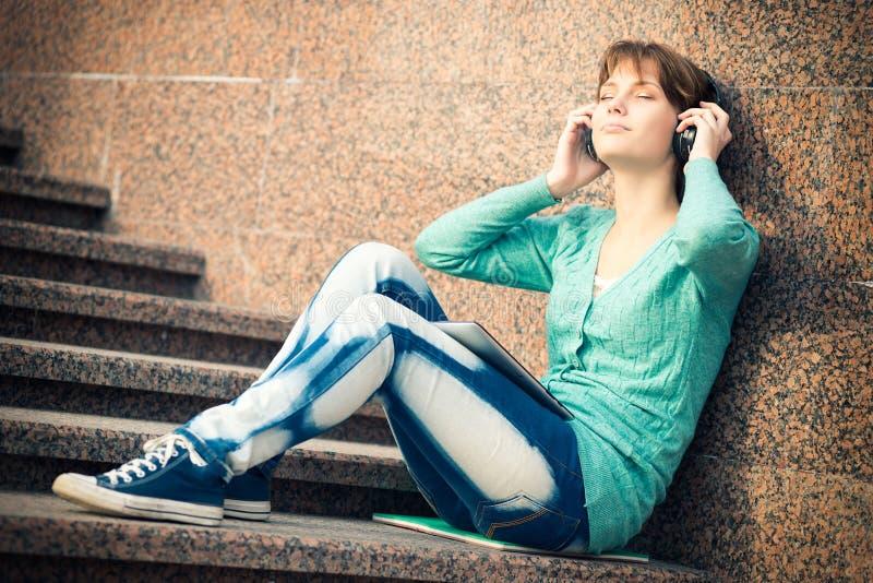 Piękny młoda kobieta uczeń z hełmofonami Plenerowa muzyczna dziewczyna zdjęcia stock