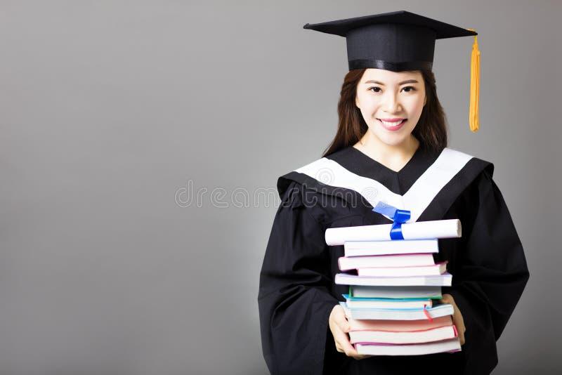 Piękny młodego absolwenta mienia dyplom i książka fotografia stock