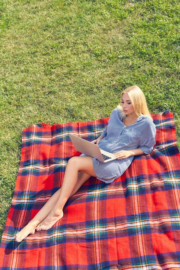 Piękny młodej dziewczyny freelancer z laptopem w parku fotografia royalty free