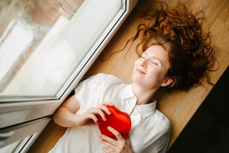 Piękny młodej dziewczyny lying on the beach okno z prezentem dla walentynka dnia zdjęcie stock