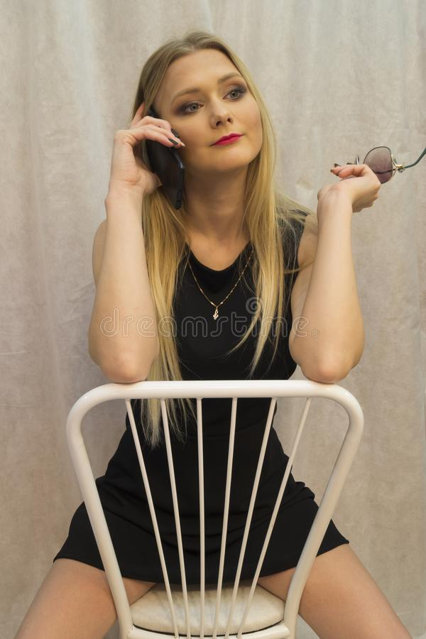 Piękny młodej dziewczyny obsiadanie na białym krześle i opowiadać na telefonie komórkowym zdjęcia stock