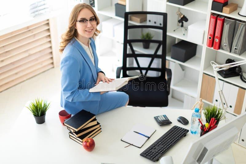 Piękny młodej dziewczyny obsiadanie przy biurkiem w biurze i mieniu otwarta książka fotografia stock