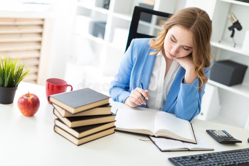 Piękny młodej dziewczyny obsiadanie przy biurkiem w biurze, mieniu i czytaniu, pióro w jej ręce książka zdjęcie stock