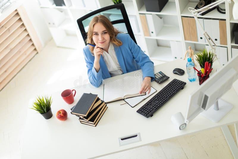 Piękny młodej dziewczyny obsiadanie przy biurkiem w biurze, mieniu i czytaniu, pióro w jej ręce książka obrazy royalty free