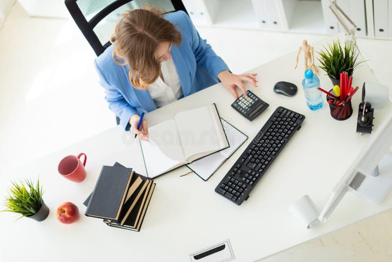 Piękny młodej dziewczyny obsiadanie przy biurkiem w biurze, mieniu i czytaniu, pióro w jej ręce książka obrazy stock