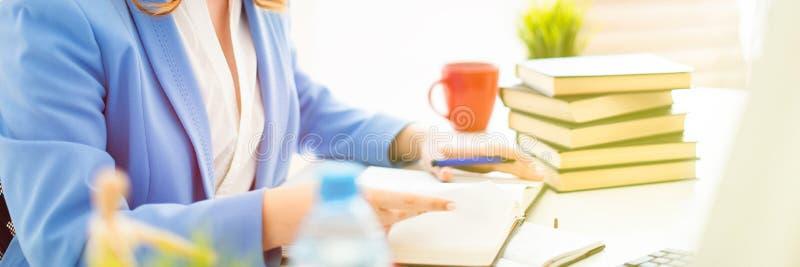 Piękny młodej dziewczyny obsiadanie przy biurkiem w biurze, mieniu i czytaniu, pióro w jej ręce książka zdjęcie royalty free