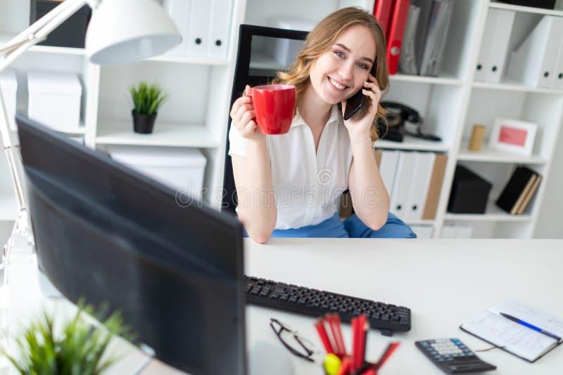 Piękny młodej dziewczyny obsiadanie w biurze, mienie kubek w jej ręce i opowiadać na telefonie zdjęcie royalty free