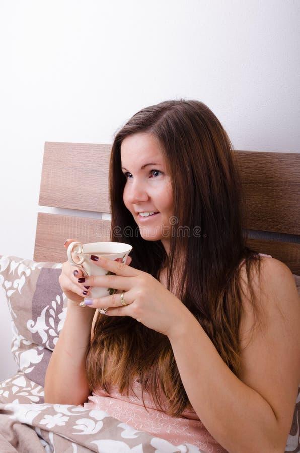 Piękny młodej kobiety łasowania śniadanie w łóżku w ranku obraz stock