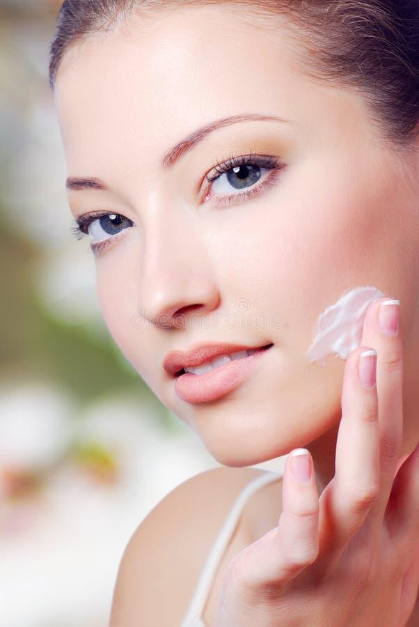Piękny młodej kobiety aplying crean na twarzy zdjęcie stock