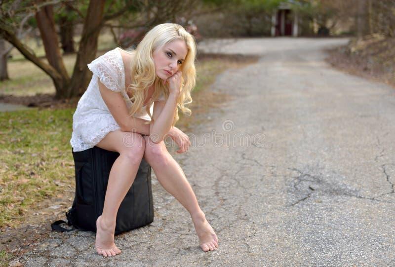 Piękny młodej kobiety czekanie drogą dla przejażdżki zdjęcia stock