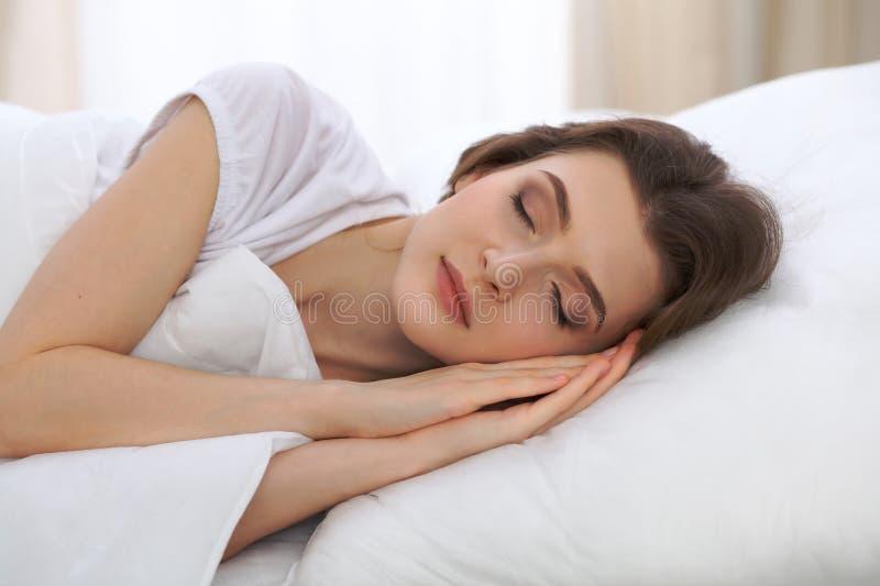 Piękny młodej kobiety dosypianie podczas gdy kłamający w jej łóżku i relaksujący swobodnie Ja jest łatwy budził się dla pracy lub zdjęcia royalty free