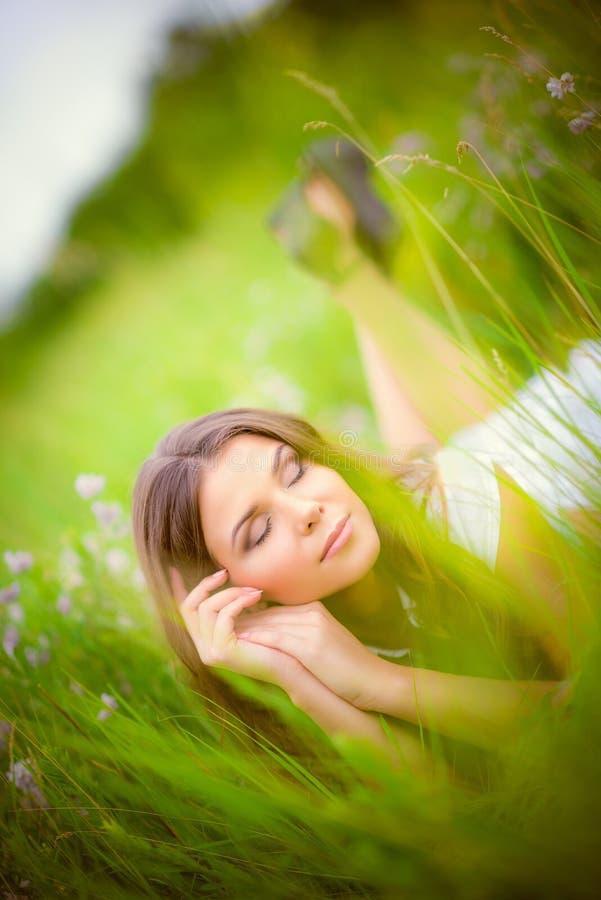 Piękny młodej kobiety dosypianie wśród trawy i kwiatów fotografia stock