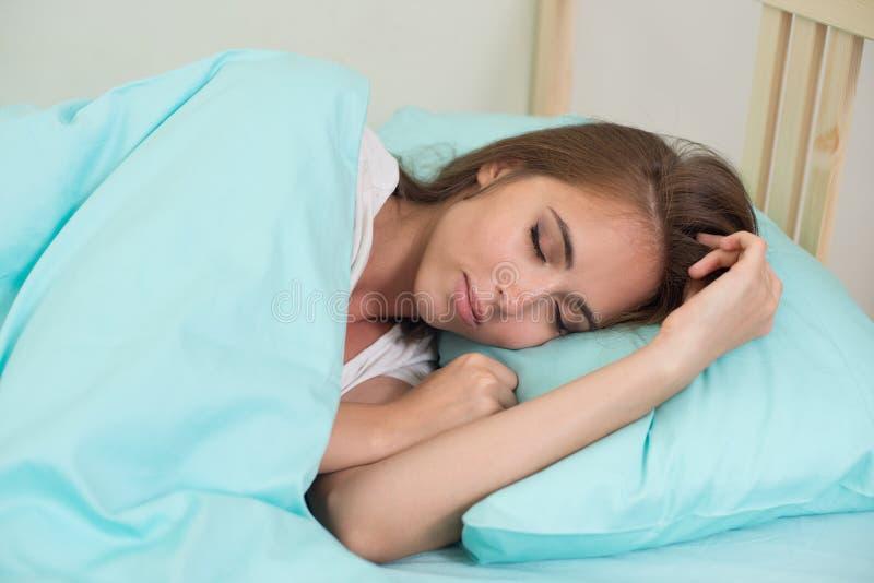 Piękny młodej kobiety dosypianie w łóżku pod błękitnym duvet z rękami blisko ona w domu twarz zdjęcia stock