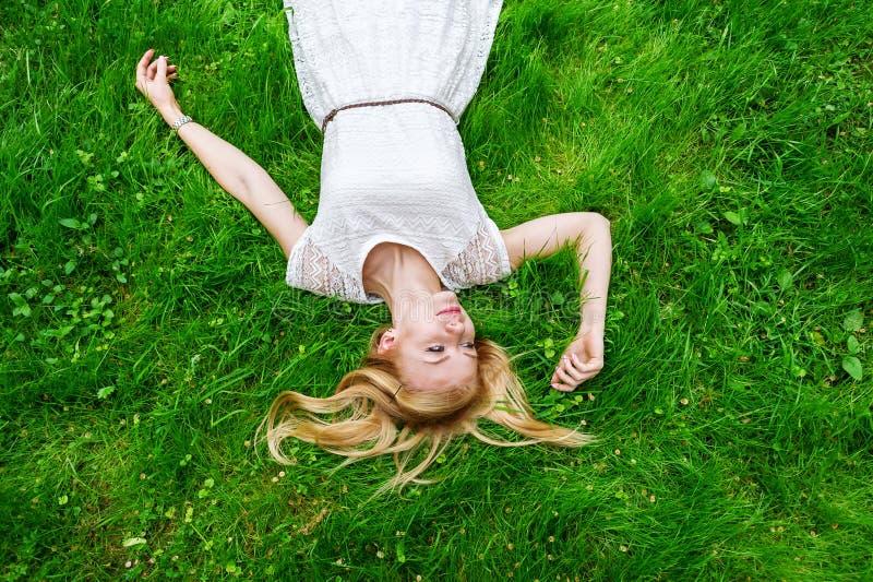 Piękny młodej kobiety lying on the beach na jaskrawym - zielona trawa zdjęcie royalty free
