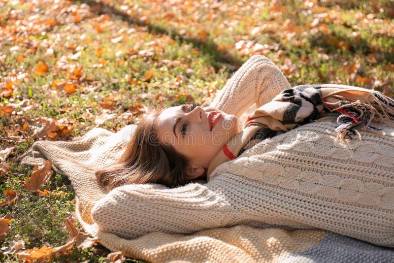Piękny młodej kobiety lying on the beach na szkockiej kracie w jesień parku obraz stock