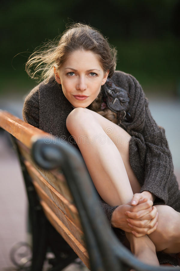 Piękny młodej kobiety obsiadanie na ławce zdjęcia royalty free