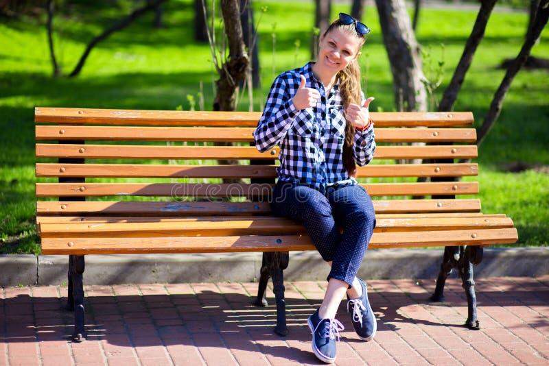 Piękny młodej kobiety obsiadanie na ławce w miasta przedstawienia i parka aprobatach zdjęcia royalty free