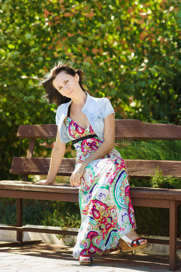 Piękny młodej kobiety obsiadanie na ławce w miasto parku obrazy stock