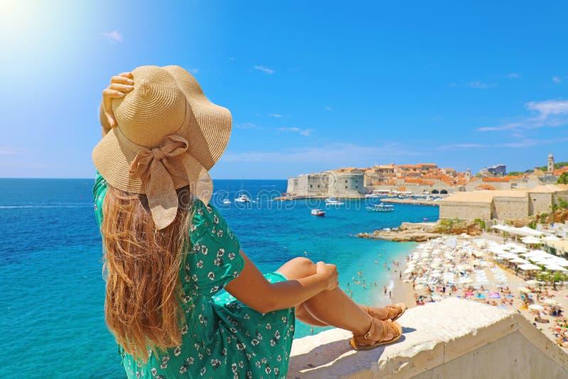 Piękny młodej kobiety obsiadanie na ściennym patrzeje oszałamiająco widoku morza śródziemnomorskiego i Dubrovnik stary miasteczko obraz royalty free