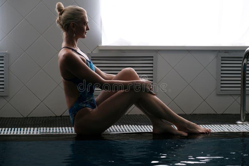 Piękny młodej kobiety obsiadanie na krawędzi basenu w profilu obraz stock