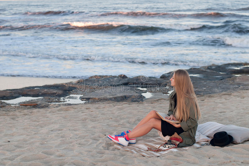 Piękny młodej kobiety obsiadanie na plaży, patrzeje fala obrazy royalty free