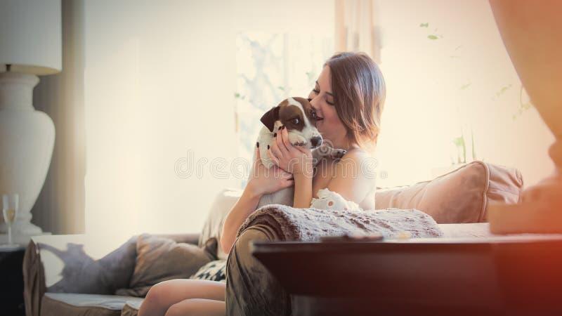 Piękny młodej kobiety obsiadanie na przytuleniu i kanapie jej pies wewnątrz obrazy royalty free