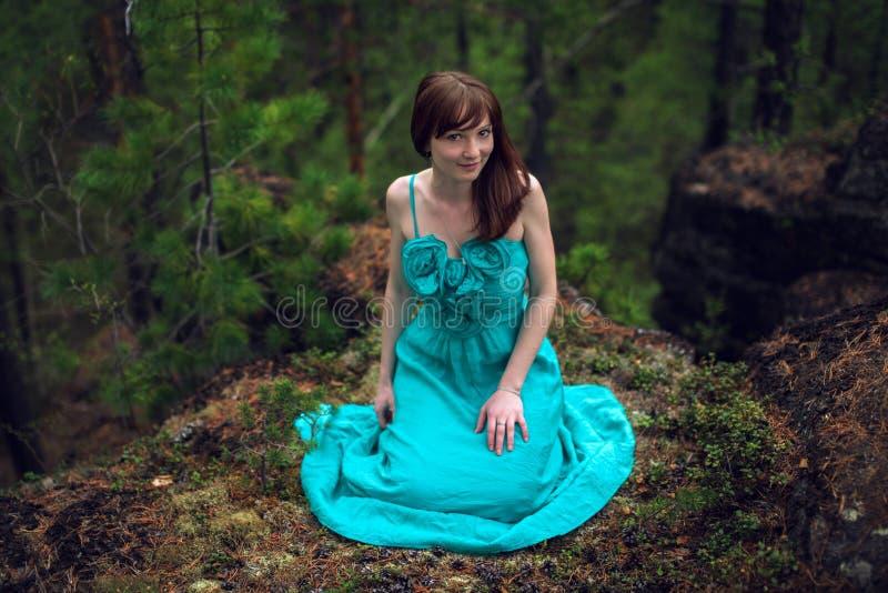 Piękny młodej kobiety obsiadanie na skale w drewnach zdjęcia royalty free